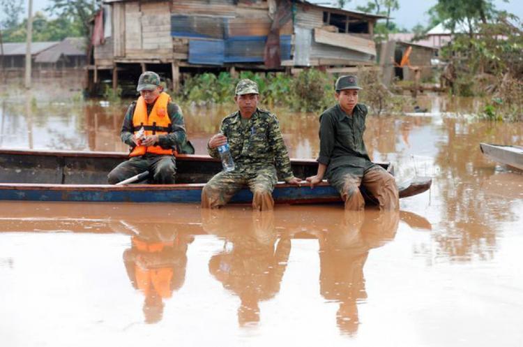 Các binh sĩ Lào ngồi trên thuyền khi cứu trợ người dân tại vùng bị ngập lụt. Truyền thông Lào đưa tin có 27 người thiệt mạng sau sự cố vỡ đập. Ảnh: Reuters