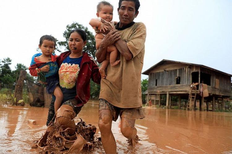 Một gia đình lội bùn trở về nhà. Ảnh:Reuters