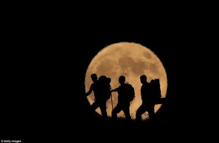 3 người đang leo núi Artos ở Thổ Nhĩ Kỳ khi Mặt Trăng tỏa sáng phía sau họ. Ảnh: Getty