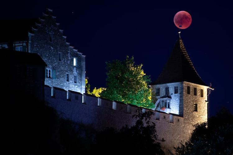 """Mặt Trăng to và đẹp """"đậu"""" trên tháp chuông của Lâu đàiLaufen, Thụy Sĩ. Ảnh: EPA"""