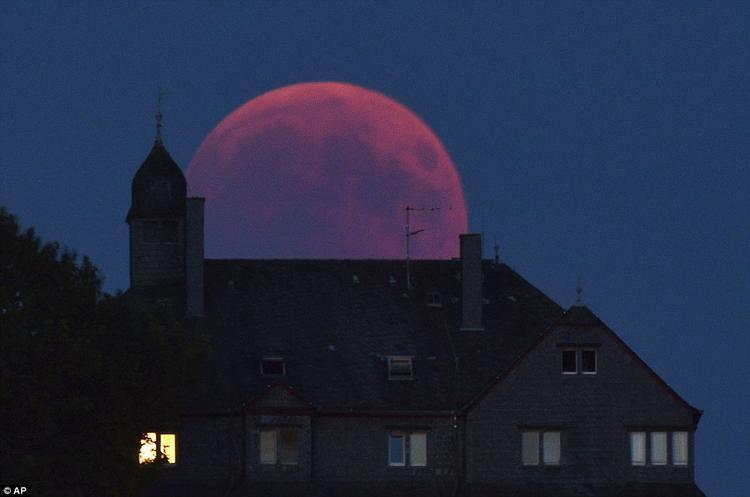 Mặt Trăng chuyển màu đỏ trên bầu trời Bernkastel-Kues, Đức. Cùng lúc với nguyệt thực, sao Hỏa xuất hiện sáng hơn bình thường. Ảnh: AP