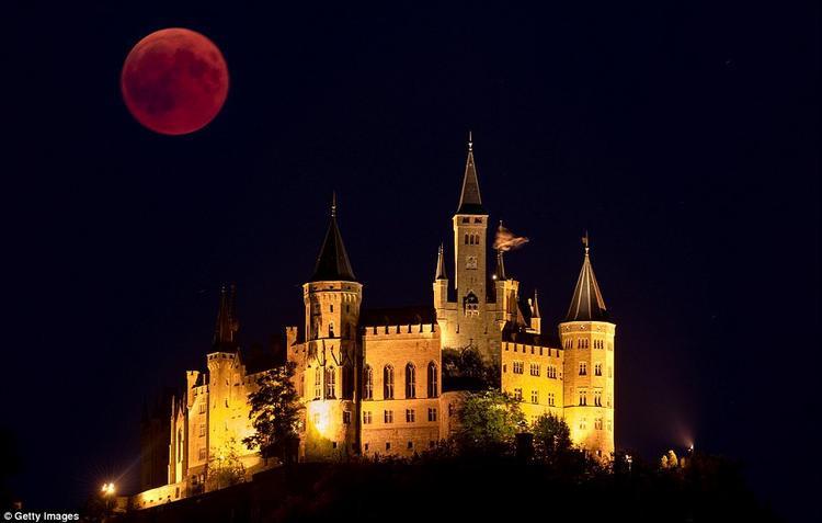 Hàng triệu người yêu thiên văn khắp thế giới, như ở châu Âu, Trung Đông, châu Á, châu Phi, một phần của Úc và Nam Mỹ, đã có một đêm tuyệt vời khi chứng kiến hiện tượng nguyệt thực dài nhất thế kỷ. Thời gian diễn ra nguyệt thực là từ 00h14 đến 6h28 (dài hơn 5 tiếng) và nguyệt thực toàn phần kéo dài 1 tiếng 43 phút, bắt đầu từ 2h30. Trong ảnh, Mặt Trăng tròn vành vạnh mọc phía sau Lâu đài Hohenzollern ở Hechingen, Đức. Ảnh: Getty