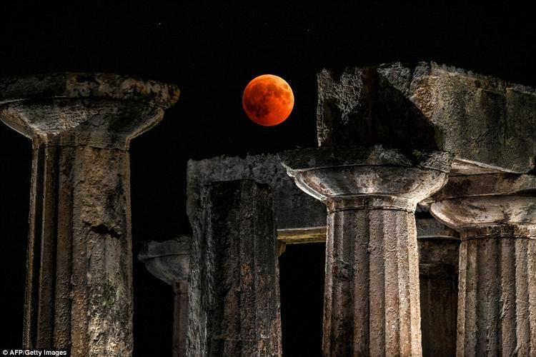 """Một góc đền thờ Apollo ở Corinth, Hy Lạp với """"Trăng máu"""". Các nhà khoa học cho biết sở dĩ Mặt Trăng có màu đỏ trong nguyệt thực toàn phần là do một hiệu ứng có tên là tán xạ Rayleigh. Ảnh: AFP/Getty"""