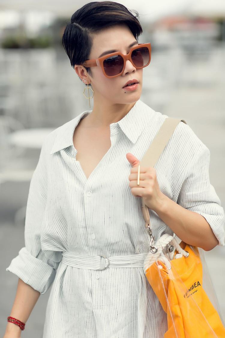 Cô kết hợp thêm phụ kiện túi trong suốt hot nhất hè này cùng mắt kính to bản khiến set đồ thêm phần thu hút.