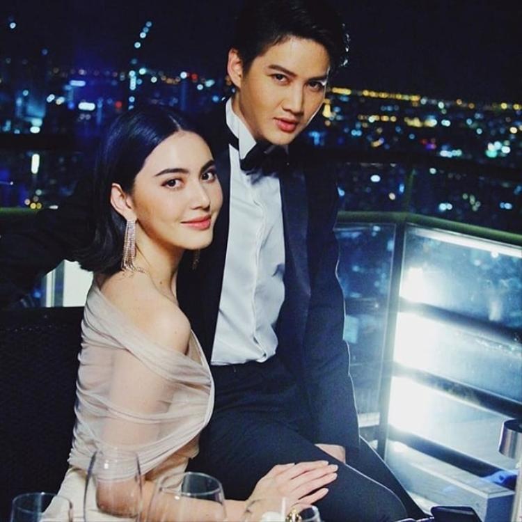 Cả hai ăn tối dưới ánh nến lung linh trên một tòa nhà cao tầng.