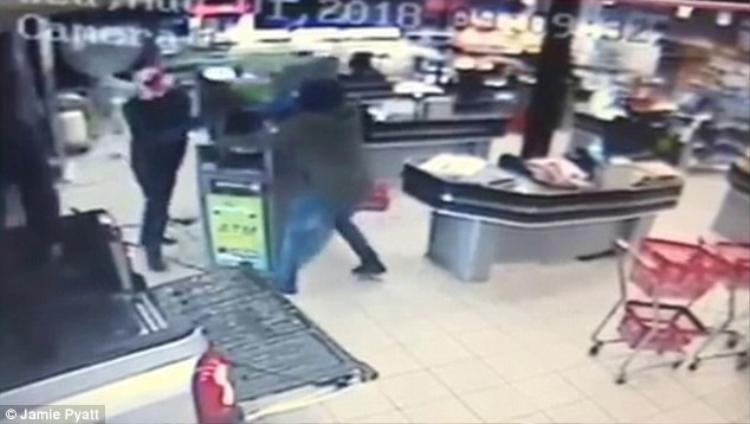 Nhóm cướp di chuyển cây ATM trên sàn và khiêng lên thùng xe bán tải.