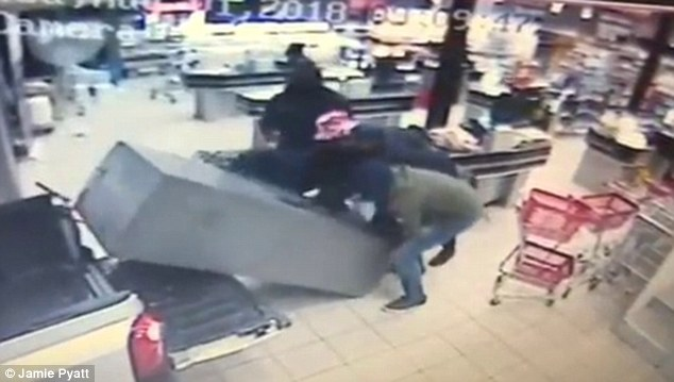 Nhóm cướp cố gắng nâng máy rút tiền vào cốp xe bán tải.