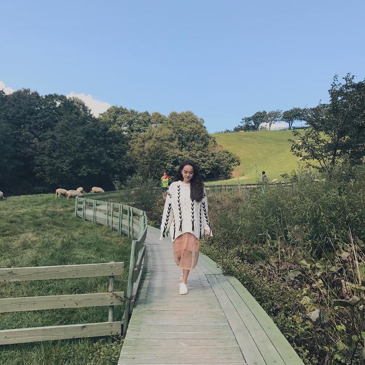 Sự kết hợp độc đáo giữa áo len oversize và chân váy dài. Cô chọn kiểu tóc xoăn sóng rất Tây tạo cảm giác tự do, phóng khoáng.