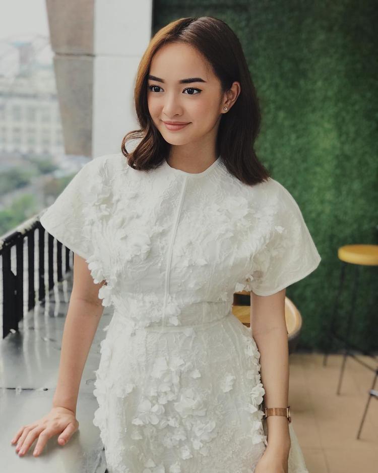 Dịu dàng trong 1 chiếc đầm trắng trang nhã kiểu dáng đơn giản nhưng được phối ren và đính hoa nổi cầu kì.