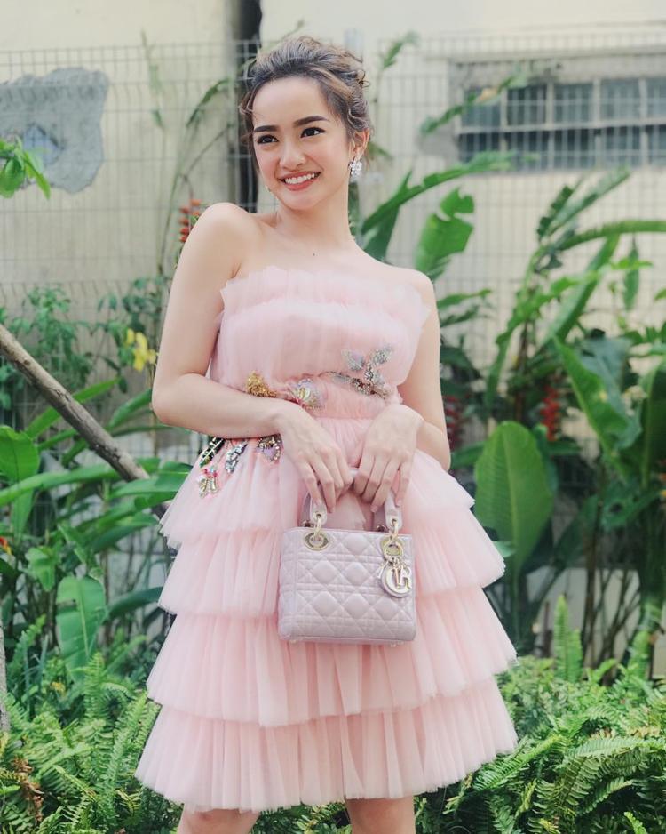 Nữ diễn viên như hóa thành nàng công chúa xinh xắn, rạng rỡ trong chiếc đầm hồng pastel nhẹ nhàng. Thiết kế mang kiểu dáng cúp ngực, chất liệu voan mỏng được xếp tầng vô cùng duyên dáng.