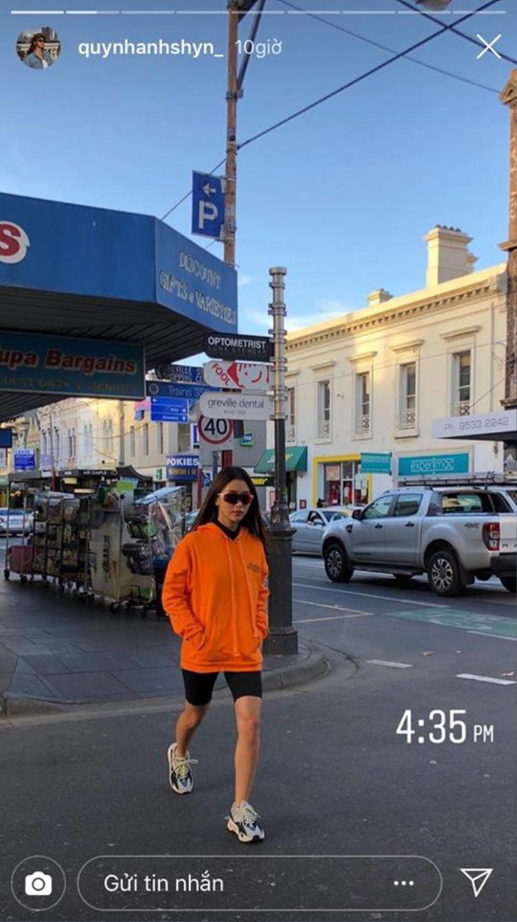 Quỳnh Anh Shyn nổi bần bật trên phố với set đồ đậm chất sporty khi mặc áo hoodie rộng màu cam tươi, quần đua xe khoe bắp vế.