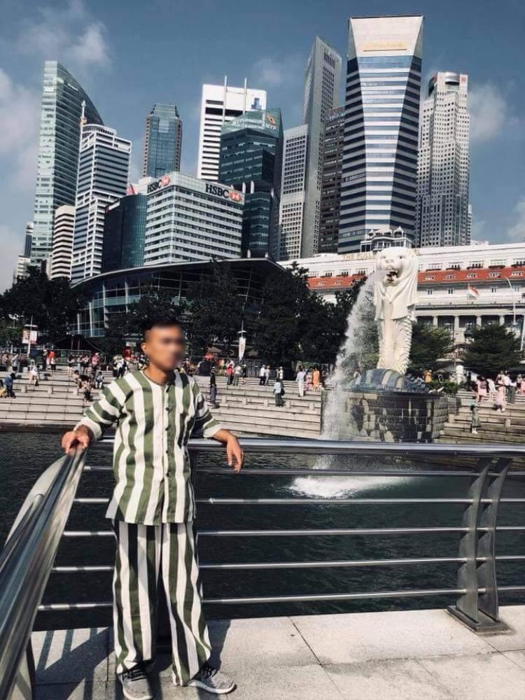 Hình ảnh thanh niên mặc bộ quần áo kẻ sọc, đứng chụp ảnh ở một vài địa điểm nổi tiếng ở Singapore.