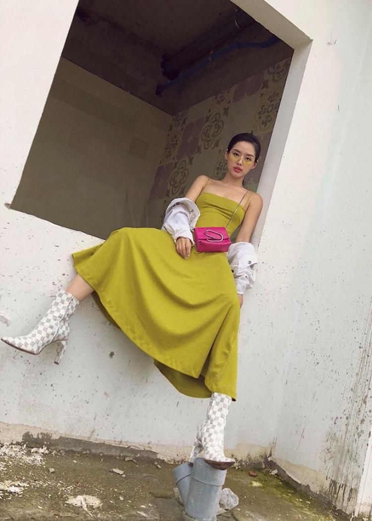 Vẻ lạnh lùng pha lẫn vẻ quyến rũ, gợi cảm. Người đẹp sinh năm 1995 nổi bật với set đồ thời thượng khi chọn màu vàng trendy kết hợp cùng boots nhọn họa tiết caro, nhấn nhá bằng túi xách mini màu hồng.
