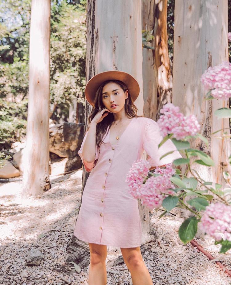 Beauty blogger Jenn Im đem đến set đồ theo phong cách đồng quê với chiếc đầm ngắn cài khuy màu hồng pastel và mũ rộng vành.