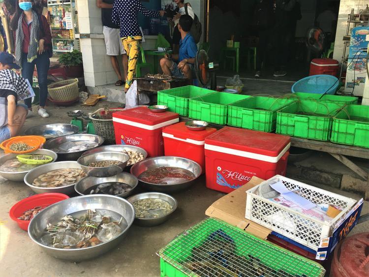 Hải sản được người dân bày bán trong ngày, phía bên trong là khu chế biến và quán ăn