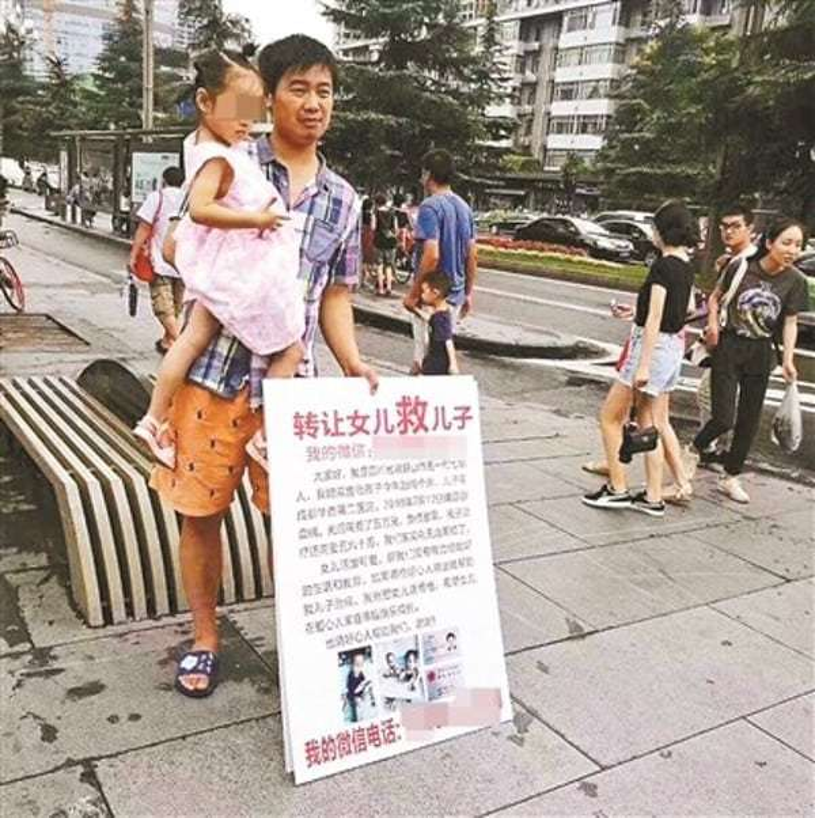 Bố mang tấm biển, rao bán con gái ngoài đường.