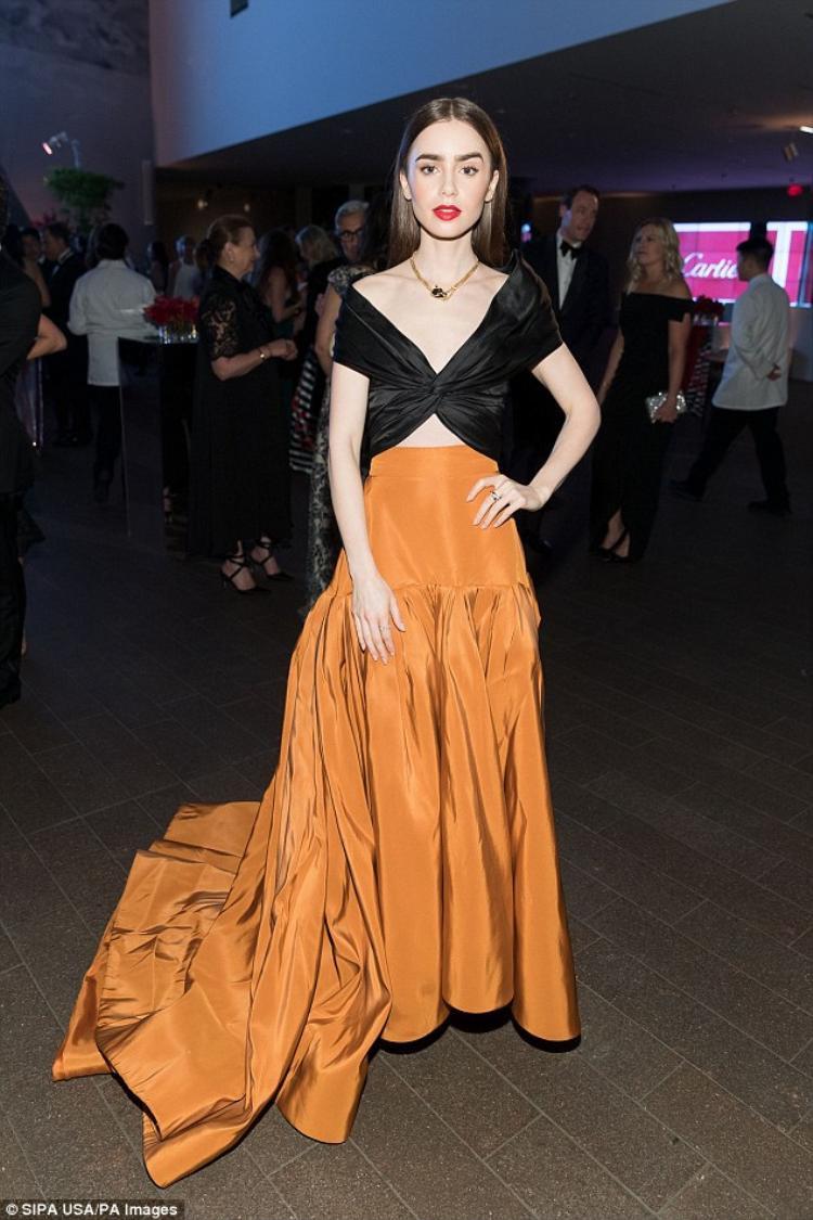 Nàng diễn viên xinh đẹp Lily Collins trông thật nổi bật và phá cách tại sự kiện với thiết kế áo crop-top đen cùng phần váy dài màu cam đất Terracotta.