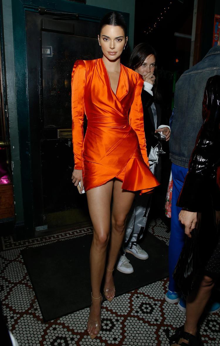Siêu mẫu Kendall Jenner thu hút mọi ánh nhìn khi diện đầm ngắn màu cam đất với cổ xẻ sâu và chi tiết bèo xếp phong cách