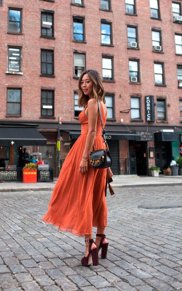 Fashionista Aimee Song chọn cho mình thiết kế đầm chiffon dài xếp li nữ tính màu cam đất với chất liệu mỏng nhẹ để dạo phố.