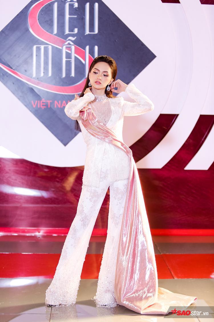 Điểm nhấn của bộ suit này chính là dải vải ánh kim màu hồng vắt chéo trên áo vest vô cùng độc đáo.