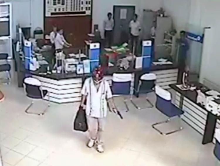Tên cướp sau lấy được tiền đã nhanh chóng ra xe tẩu thoát. Ảnh cắt từ clip.