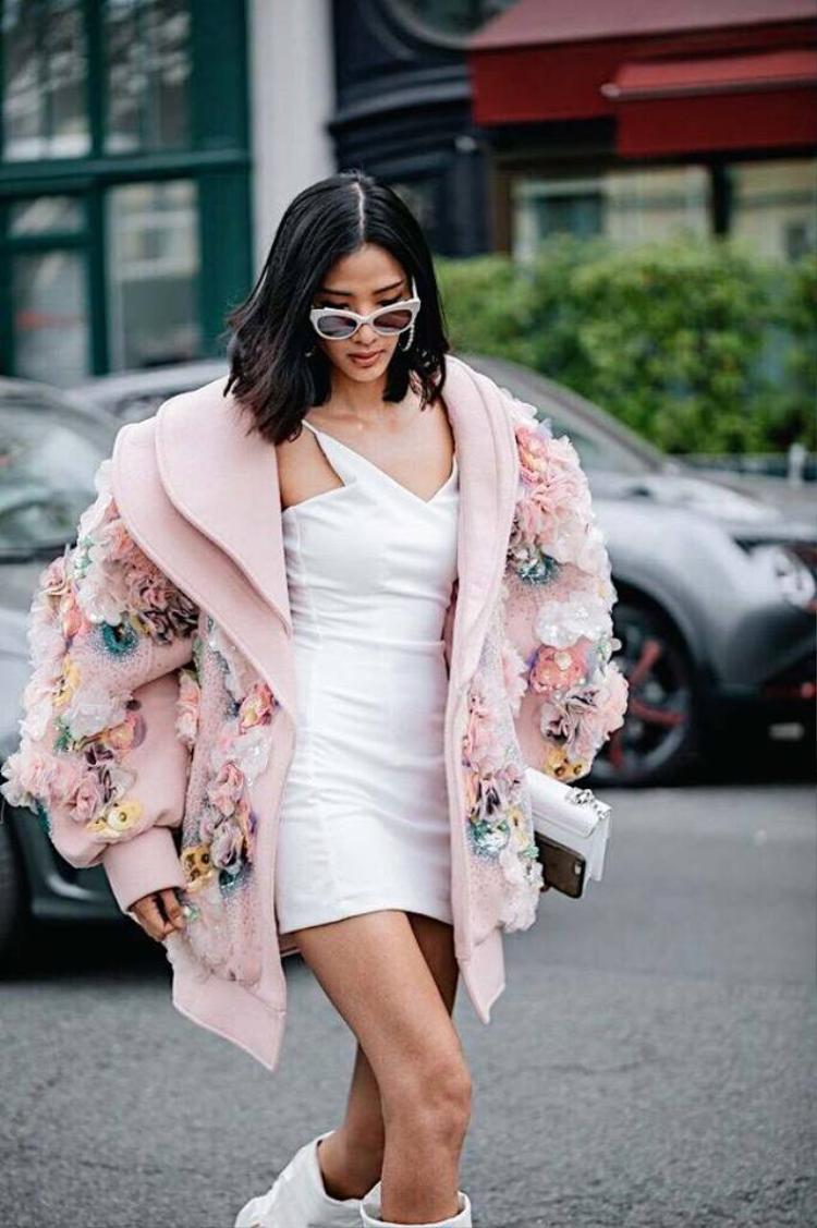 Bên trong chiếc áo khoác là một chiếc đầm trắng ngắn ôm sát, kết hợp với các phụ kiện như kính mát mắt mèo và đôi boots trắng cổ cao