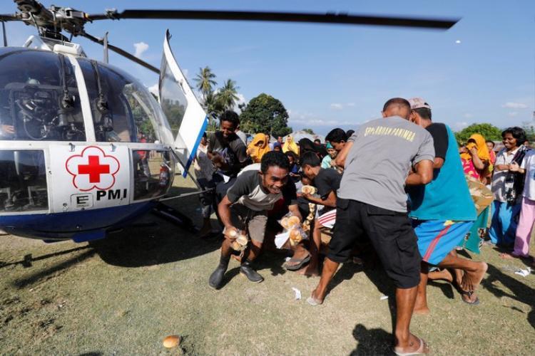 Khi trực thăng tiếp tế đến, như một phản xạ tự nhiên, người dân liền lao ra để tranh giành đồ ăn.
