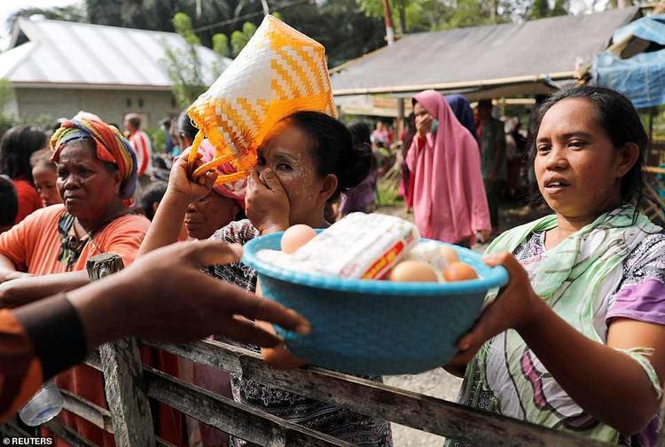 Người dân xếp hàng nhận đồ cứu trợ.