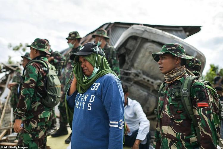 """Hơn một tuần sau thảm họa kép, hàng ngàn người ở Palu vẫn rơi vào tình trạng """"màn trời chiếu đất"""". Có người vẫn nơm nớp lo sợ thiên tai sẽ tiếp tục xảy ra nhưng có người lại tất tả đào bới đống đổ nát để tìm người thân trong vô vọng. Ông Munif Umayar, 50 tuổi, chia sẻ: """"Sợ rằng anh trai tôi vẫn còn mắc kẹt trong nhà, nên sau thảm họa kép xảy ra, tôi liền chạy về nhà. Tôi phải đào xuống rất sâu mới biết đây là nhà mình. Khi tìm thấy nó, tôi cắm một lá cờ lên đó như làm dấu""""."""