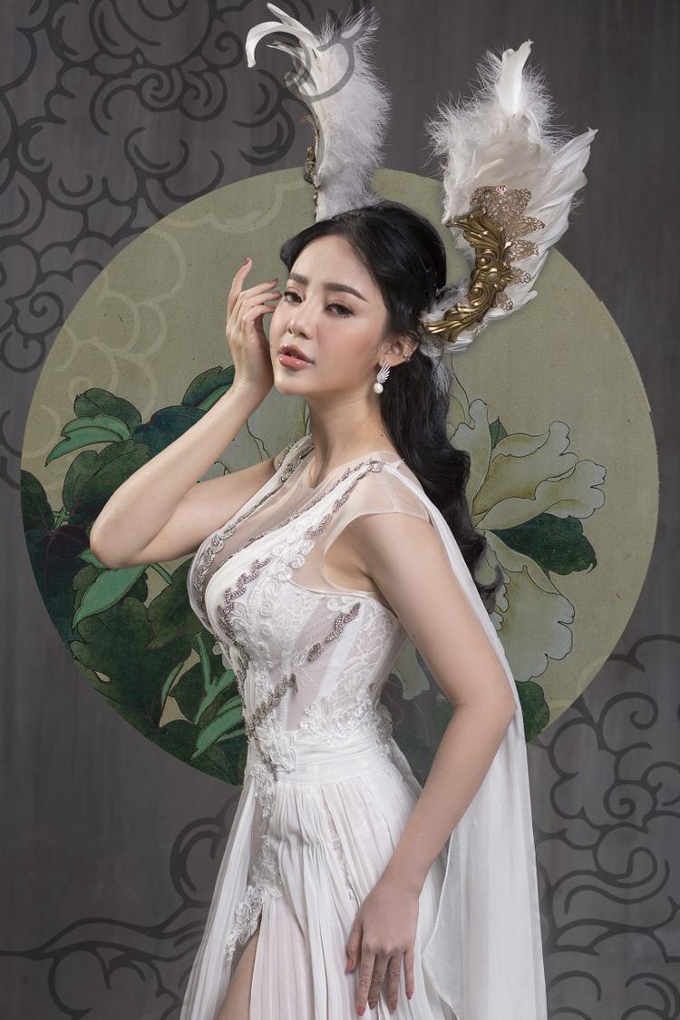 Diện thiết kế màu trắng đính kết, Ngọc Ny sử dụng thêm hai đôi cánh cài đầu để tăng phần nổi bật.