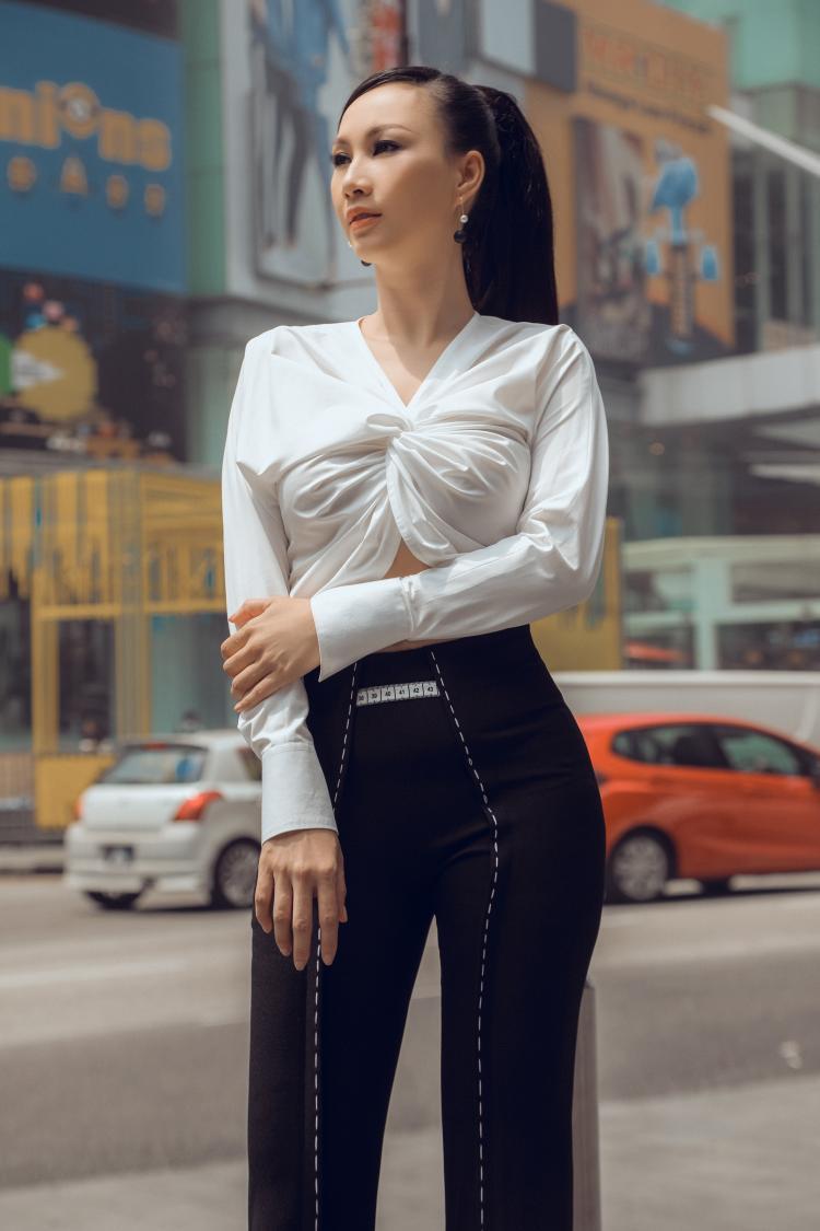 Thiết kế áo dài tay với phần co dúm ở thân trước tạo điểm nhấn tinh tế, đồng thời khoe khéo số đo vòng 2 thon gọn của bà mẹ 3 con.