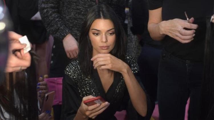 Kendall vừa trang điểm vừa lượt điện thoại