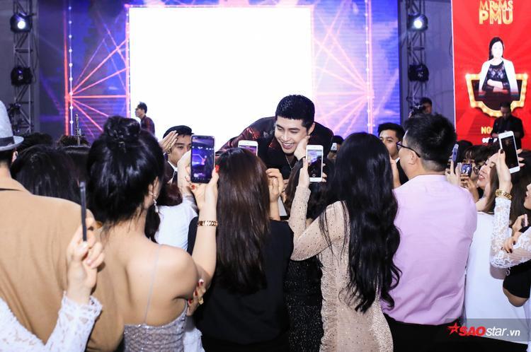 Hình ảnh Noo Phước Thịnh thân thiết để fan nựng má tại sự kiện.