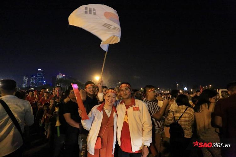 """Cả 2 cùng mặc áo đỏ, đeo băng rôn """"Việt Nam vô địch"""" như lời chúc, lời động viên đến các tuyển thủ Việt Nam."""