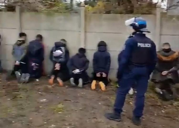Một số học sinh bị buộc úp mặt vào tường, hai tay bị còng phía sau.