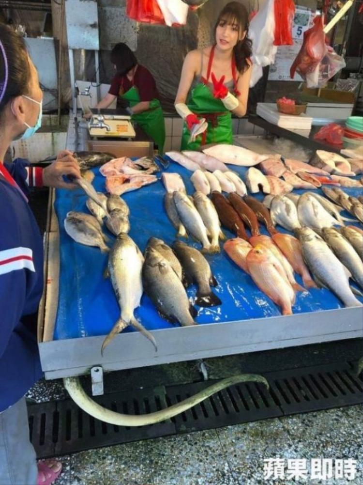Sáng 6/12, một đám đông xếp hàng trước quầy của Liu. Tuy nhiên, chỉ số ít trong đó thực sự mua cá còn những người khác dùng điện thoại chụp hình cô nàng.