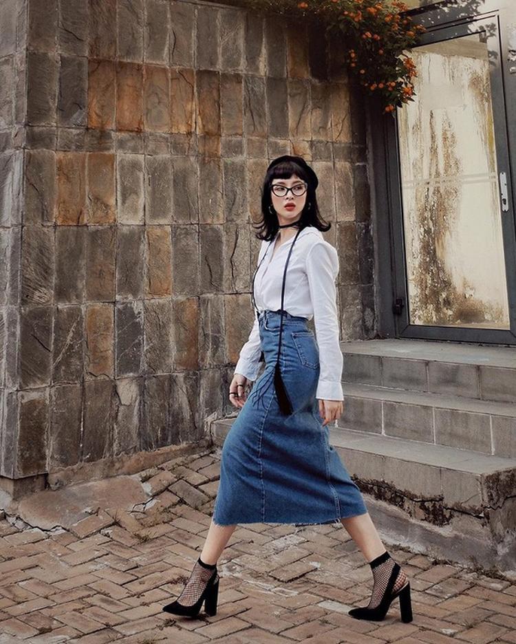 Sơ mi trắng nền nã kết hợp váy denim midi mang đậm phong cách vintage. Phụ kiện cùng mắt kiếng tí hon cùng mũ beret