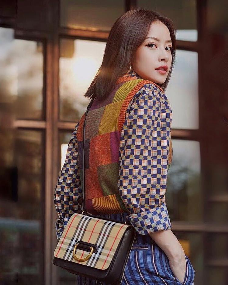 Thanh lịch trong set đồ theo xu hướng layer phá cách, Chi Pu mix áo sơ mi họa tiết cùng áo len không tay và quần kẻ sọc.