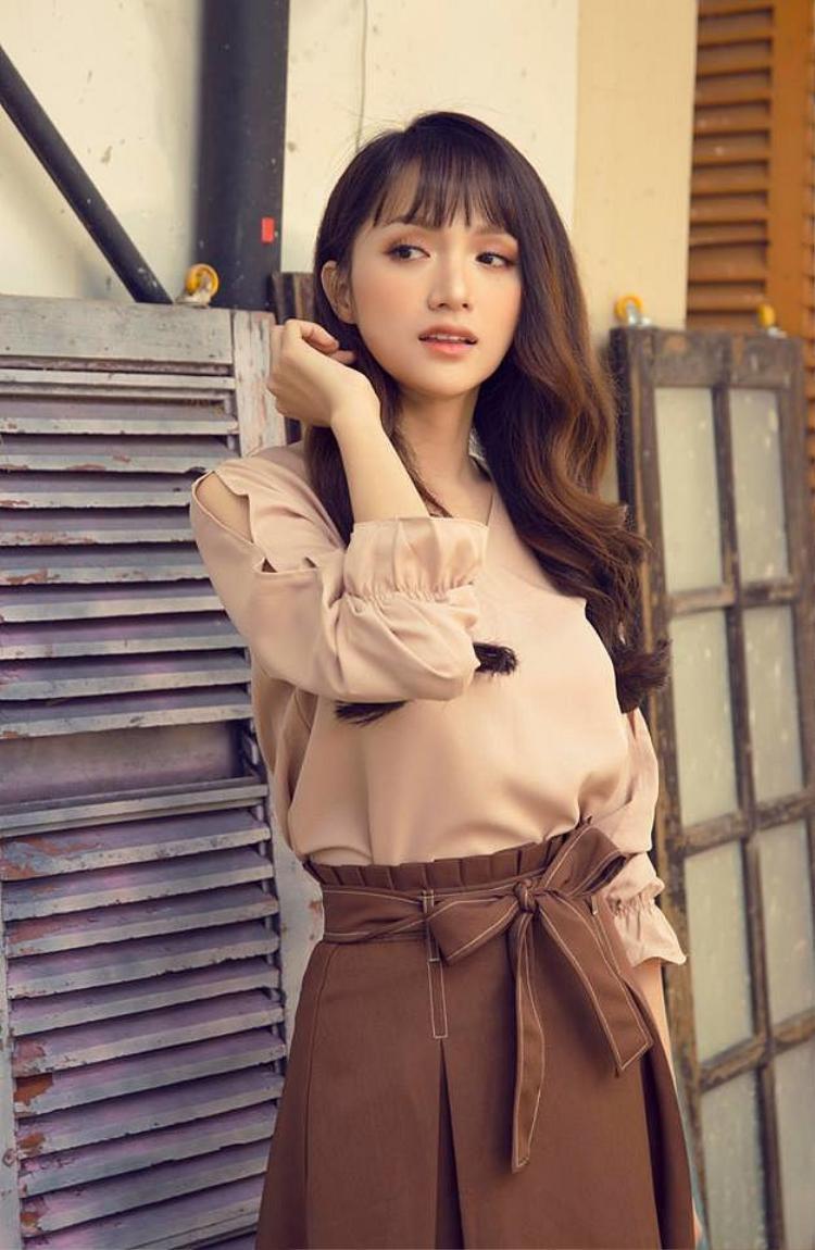 Hoa hậu Hương Giang đằm thắm áo dài tay màu be với chân váy midi đính nơ tông nâu trầm.