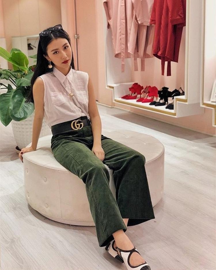 Fashionista Quỳnh Anh Shyn chọn chiếc quần xanh rêu ống rộng bằng vải nhung, kết hợp với sơ mi trắng không tay và belt to bản.
