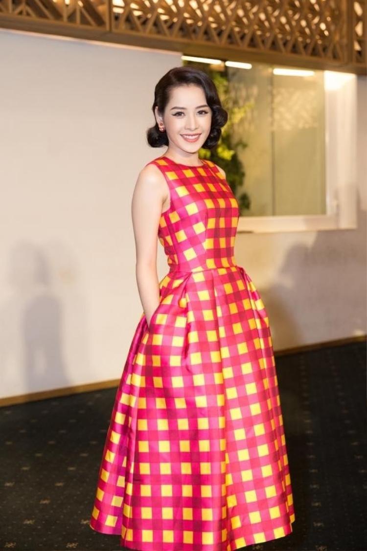 Cô nàng cổ điển trong đầm xòe caro sắc đỏ và vàng cùng kiểu tóc uốn làm tăng lên sự quý phái cho trang phục.