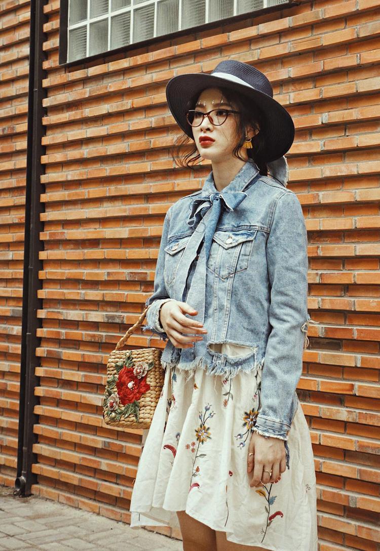 Nữ tính trong thiết kế chân váy trắng thêu họa tiết hoa kết hợp áo jacket denim thắt nơ cùng phụ kiện mũ rộng vành, giày boots nâu làm tăng hơi thở vintage