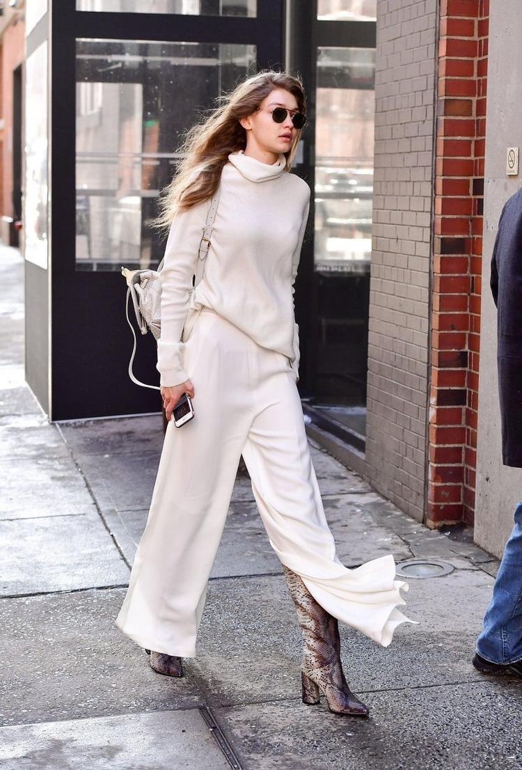 Sơvin vạt trước của áo diện cùng quần ống rộng mix cùng giày boots da trơn tạo nên tổng thể sành điệu cho cô nàng mẫu đình đám Gigi Hadid vào mùa đông này.