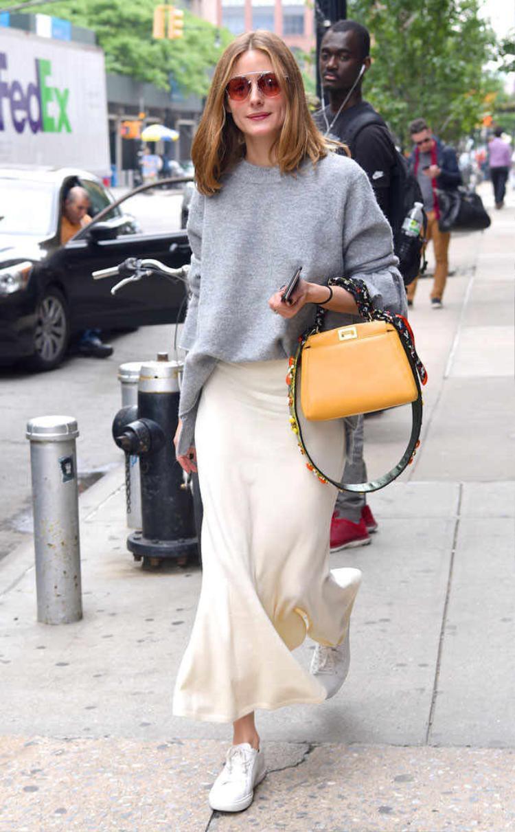 Nàng Fashionista Olivia Palermo chọn áo len oversized và chân váy thun khi xuống phố phối cùng đôi giày sneakers trắng.