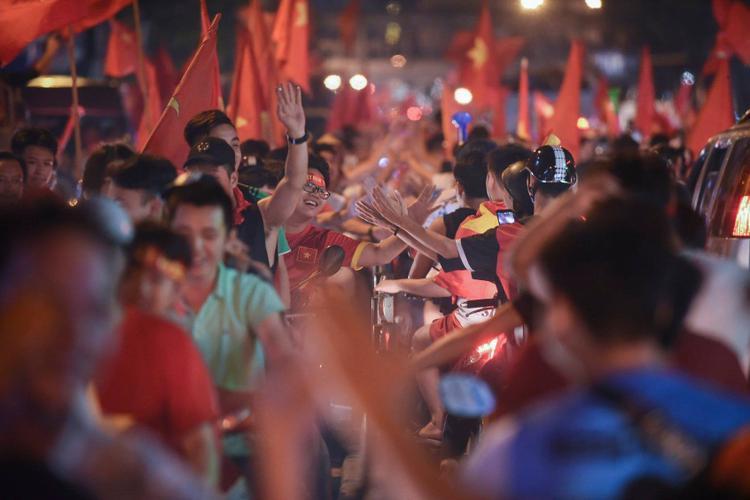 Cái bắt tay truyền nhau niềm vui của những người lạ đã thành quen.