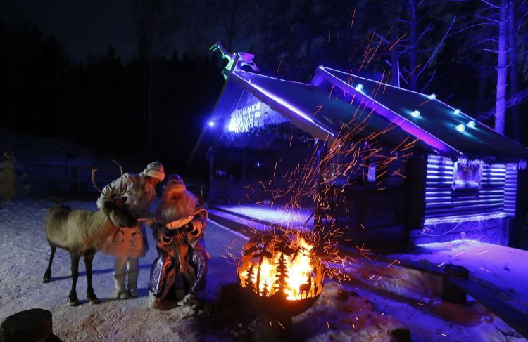 Một người đàn ông mặc trang phụcFather Frost (Ông già Tuyết tương tự như Santa Claus ở phương Tây) và người phụ nữ đóng vai cháu gáiSnegurochka đang đứng gần đống lửa trong màn biểu diễn ở công viênRoyev Ruchey, ngoại ô thành phốKrasnoyarsk của Nga ngày 12/12. Ảnh: Reuters