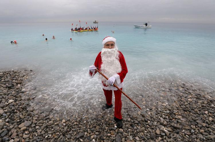 """""""Ông già Tuyết"""" đứng trên bờ trong khi nhiều người khác đang ở dưới nước. Họ đang có mặt ở một sự kiện bơi truyền thống dịp Giáng sinh ở sông Nice, Pháp ngày 16/12. Ảnh: Reuters"""