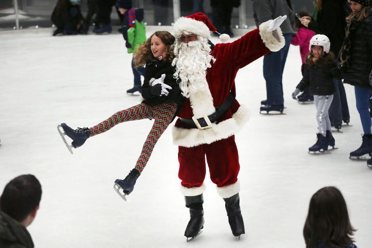 """""""Ông già Tuyết"""" bế bé gái tại sân trượt băngThe Rink at Rockefeller Center, thành phố New York, Mỹ ngày 14/12. Ảnh: Getty"""