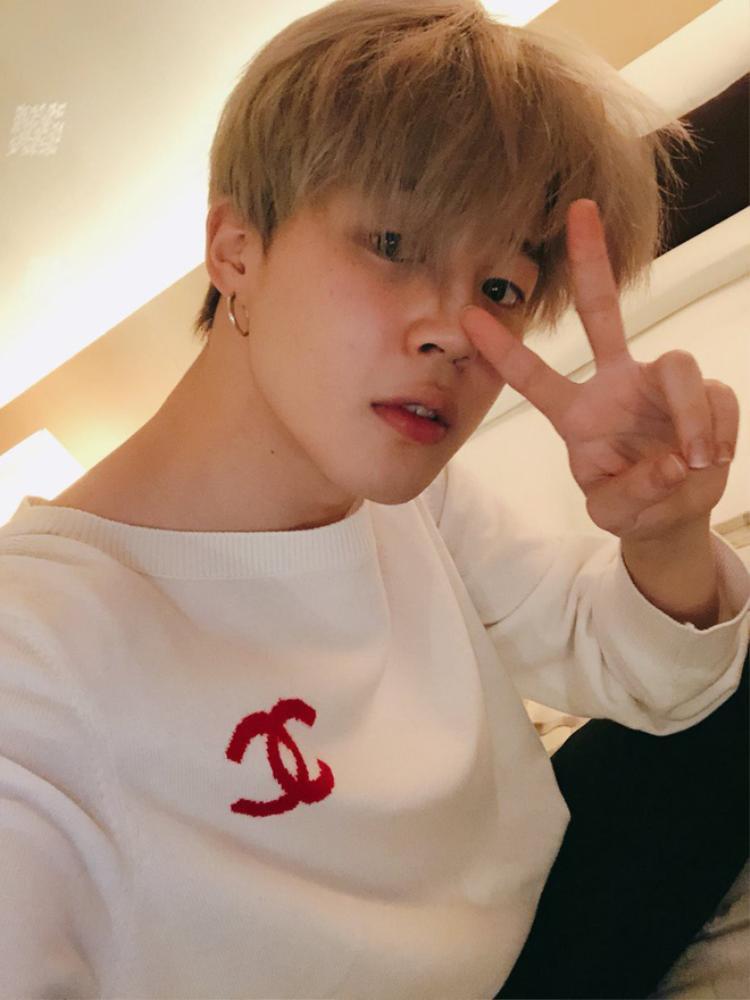 Jimin (BTS) trong chiếc áo trắng tay dài với logo màu đỏ của nhà mốt Chanel.