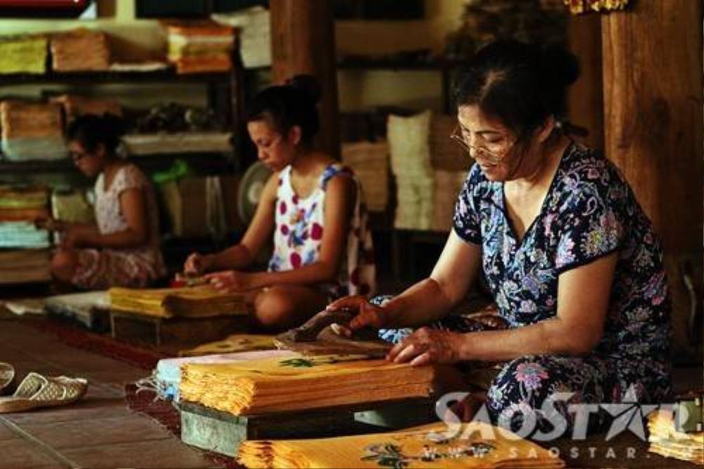 Cô Dung đang ngồi in ván màu cho tranh. Đây được xem là công đoạn cuối cùng của quy trình làm tranh.